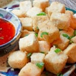 crispy tofu cubes on a plate with a side of sweet chili sauce