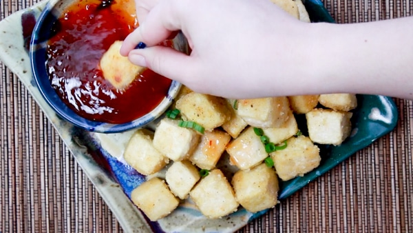 crispy tofu cubes on a plate with a woman's hand dipping one piece into a chili sauce
