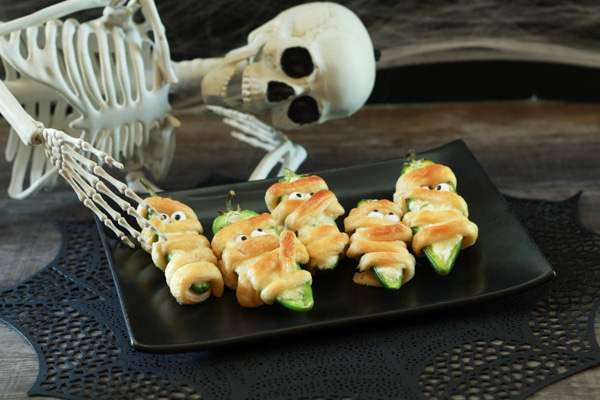 Scary Halloween Jalapeño Popper Mummies on a black plate with a skeleton sitting behind.