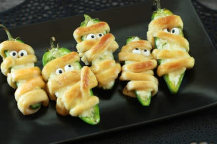 Scary Halloween Jalapeño Popper Mummies on a black plate