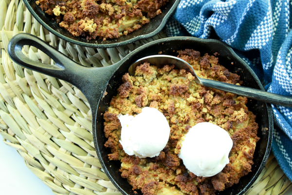 apple crisps topped with vanilla ice cream in mini cast iron skillets with a spoon and napkin on the side