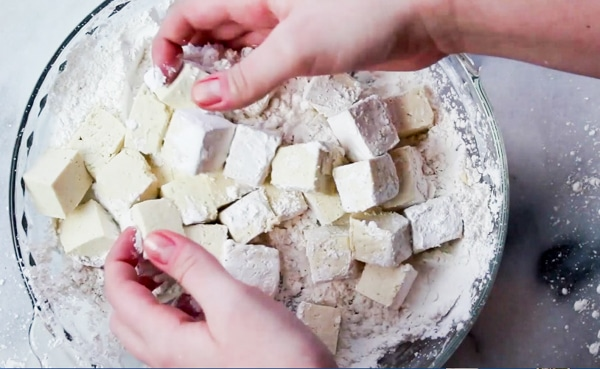 tofu cubes being tossed into corn starch in a glass bowl