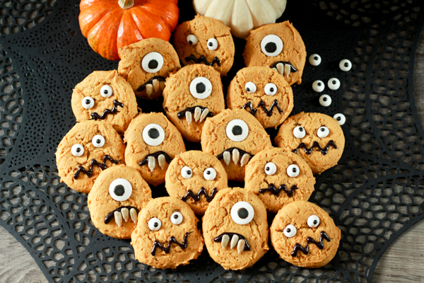 pumpkin monster cookies on a black place mat with baby pumpkins