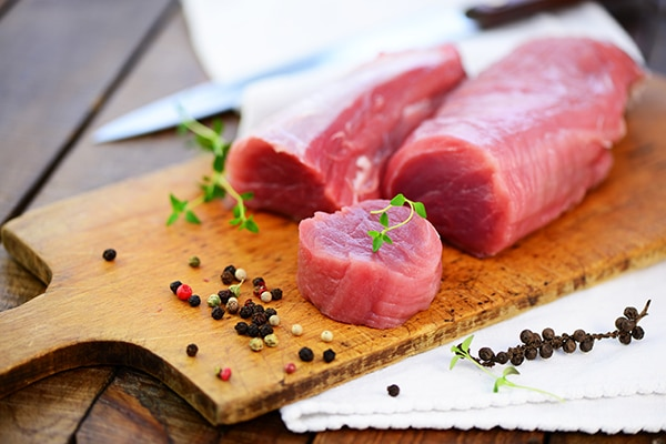 raw pork tenderloin on a wooden cutting board