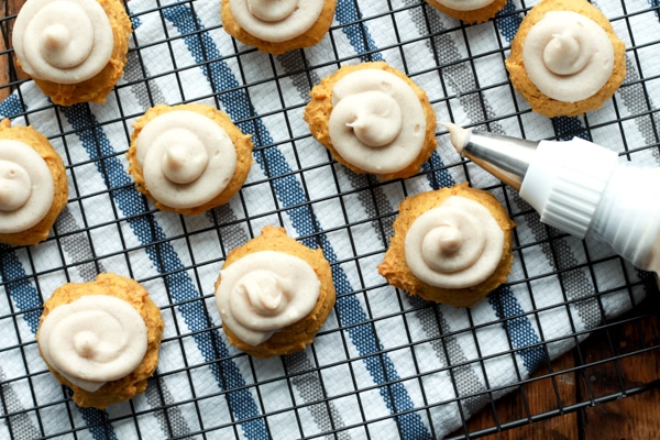 pumpkin spice cookies topped with cream cheese frosting on a baking rack