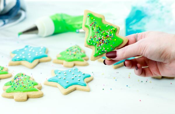 woman holding up a sugar cookie with green glaze shaped like a Christmas tree
