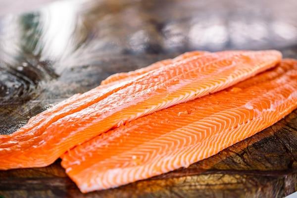 raw salmon filets on a wooden board