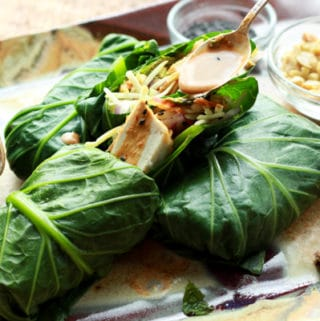 tofu collard wraps on a platter with peanut sauce being poured on top