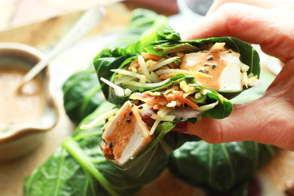 a hand holding collard green wrap stuffed with tofu and broccoli slaw and peanut dressing
