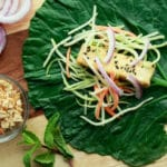 collard green leaves with crispy tofu and broccoli slaw with peanut dressing on the side