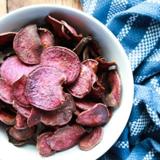 purple sweet potato chips in a white bowl with a blue napkin along side