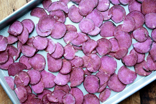 slices of purple sweet potatoes on a large baking sheet