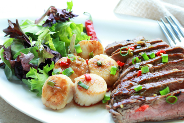 seared scallops and grilled flank steak on a white plate with a green salad on the side