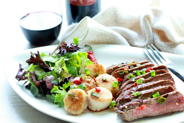 Seared scallops and grilled flank steak on a white plate with a bottle and glass of red wine