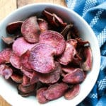 baked purple sweet potato chips in a white bowl with a blue napkin along side