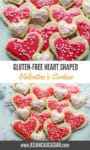 Decorated pink heart-shaped sugar cookies are stacked together.