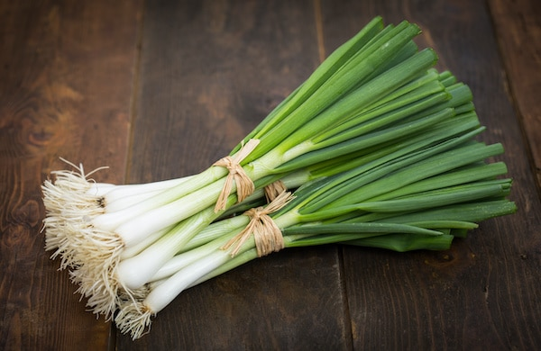 green onions bundled together on a wooden board