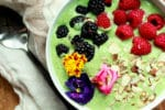 a green smoothie bowl topped with raspberries, blackberries, almonds and edible flowers