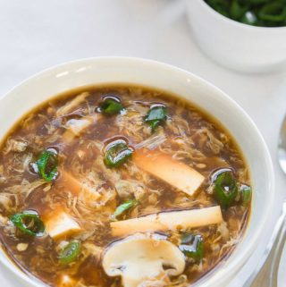 hot and sour soup in a white bowl with chopped green onions in the background