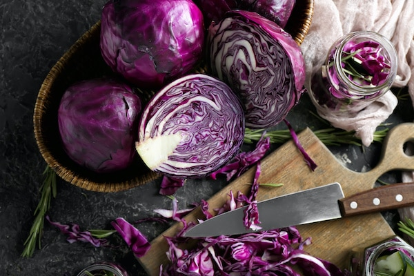 Cut red cabbage on a wooden board with a chef's knife