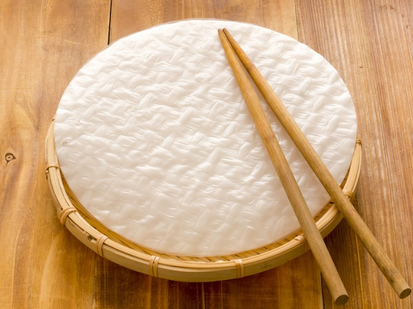 rice paper wrappers on a wooden board with chopsticks on top