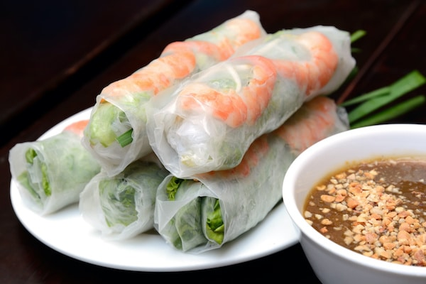 Fresh Vietnamese spring rolls on a white plate with a peanut sauce on the side