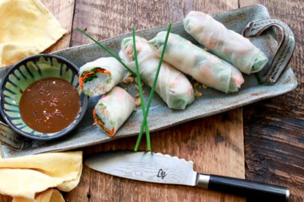 Fresh Vietnamese spring rolls on a gray platter with a peanut sauce on the side on top of a wooden board.