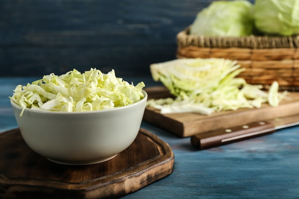 A white bowl with shredded cabbage on wooden board