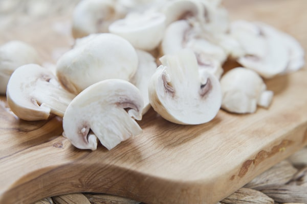 sliced button mushrooms on a wooden board