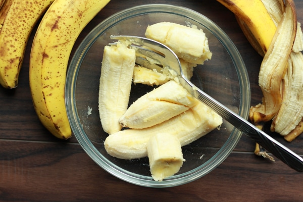 slices of banana in a glass bowl with ripe bananas on the side
