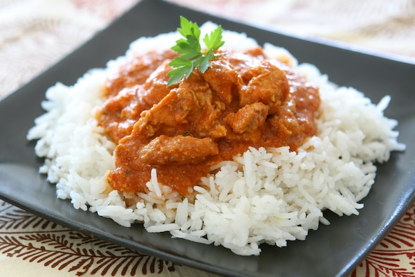 chicken tikka masala on a bed of white rice on a black square plate