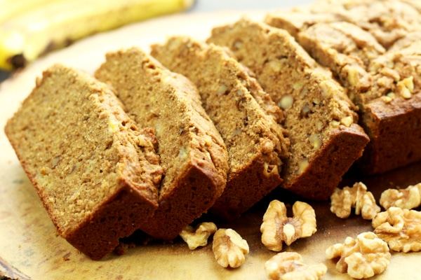 Sliced banana bread on a wooden board with walnuts and bananas on the side