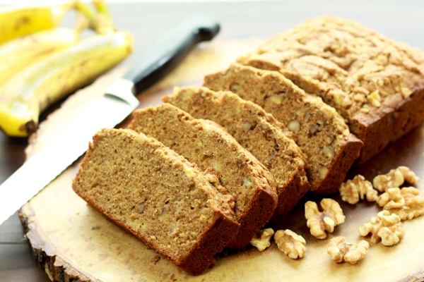 Sliced banana bread on a wooden board with walnuts and ripe bananas on the side