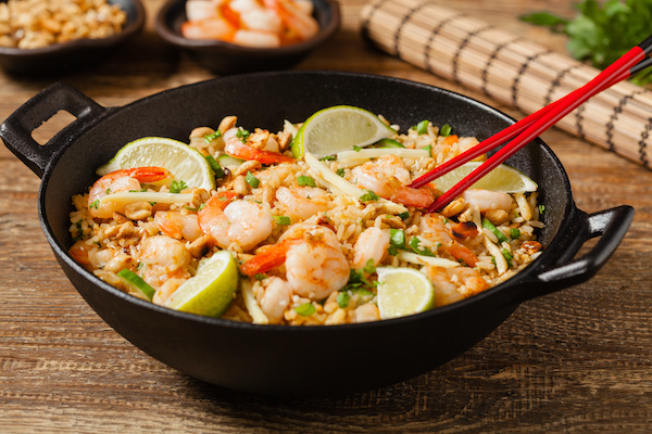 shrimp fried rice in a large black wok with red chopsticks on a wooden board