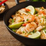 shrimp fried rice in a large black wok on a wooden board
