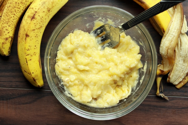 mashed bananas in a glass bowl with ripe bananas on the side