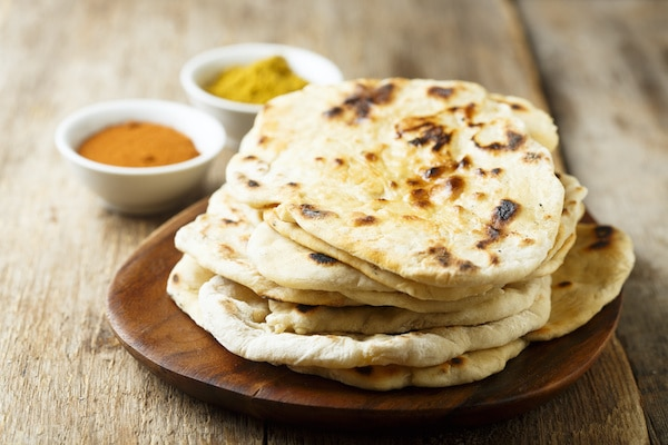 Indian naan bread stacked on a wooden board with spiced in the background