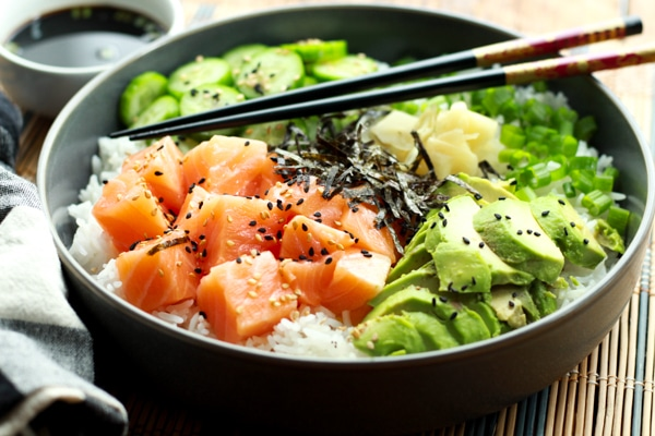 Salmon sushi bowl featuring chunks of sushi-grade salmon, sushi rice, sliced avocados, cucumbers, and seaweed strips on a bamboo mat with chopsticks.
