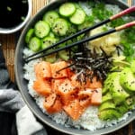 Salmon sushi bowl featuring chunks of sushi-grade salmon, sushi rice, sliced avocados, cucumbers, and seaweed strips with chopsticks.