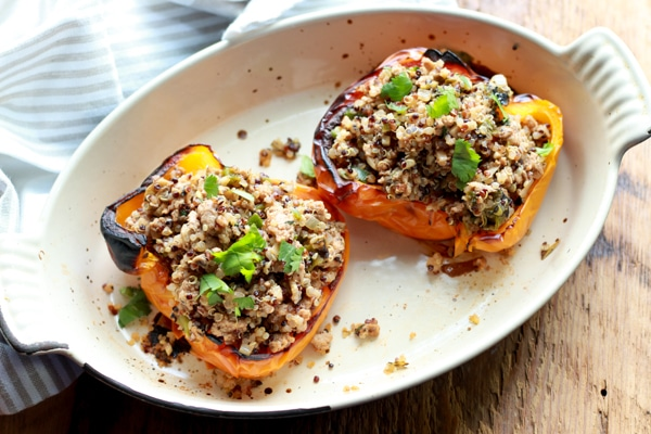 stuffed yellow bell peppers with turkey and quinoa on a white plate with a knife and fork