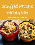 stuffed yellow bell peppers with turkey and rice on a wooden board