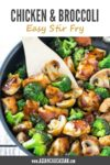 chicken and broccoli stir fry in a large wok with a wooden spatula