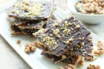chocolate covered matzo on a white plate with sprinkles of walnuts on top
