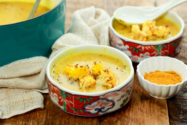 vibrant cauliflower soup in two bowls on a wooden board with turmeric powder on the side