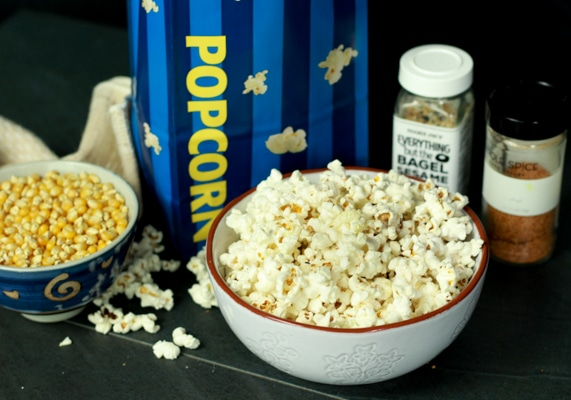 a bowl of popcorn on a black board with two seasonings behind and a bowl of kernels on the side