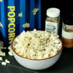 popcorn in a white bowl with two seasonings behind