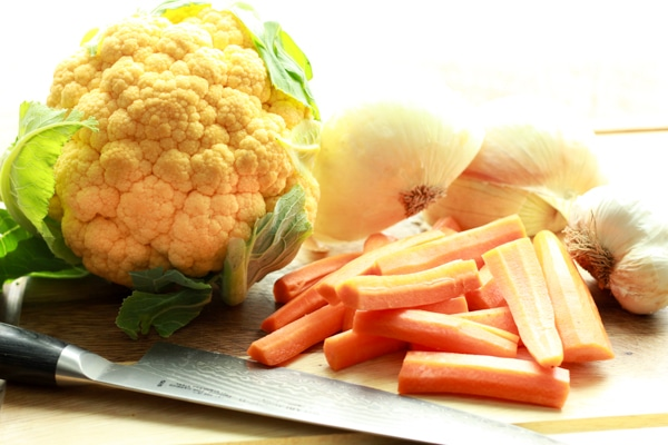 a head of orange cauliflower, carrot sticks, onions, and garlic on a wooden board with a chefs knife