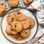 miso chocolate chip cookies on a white plate with cookies on a cooling rack behinds