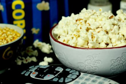 a white bowl with popcorn inside with a TV remote control in front and a bowl of unpopped kernels on the side