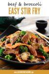 stir fry beef and broccoli in a black bowl with chopsticks